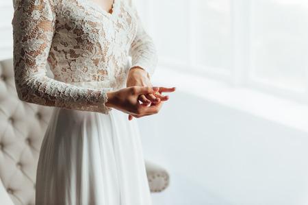 Hochzeit. Braut. Die Vorbereitungen. Hochzeitskleid. Braut im cremefarbenen Spitzenkleid steht vor dem Fenster mit den Händen gefaltet