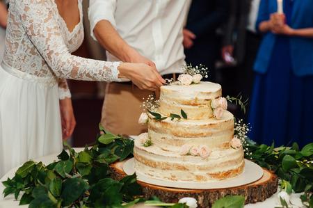 Schöne köstliche weiße Hochzeitstortezeremonie am Tisch Standard-Bild - 57737428