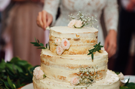 wedding table decor: Beautiful delicious white wedding cake ceremony at the table