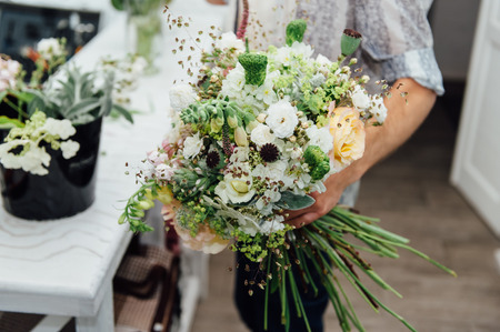 Florist finishing beautiful and rich spring flower arrangement