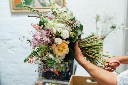 Florist finishing beautiful and rich spring flower arrangement Foto de archivo