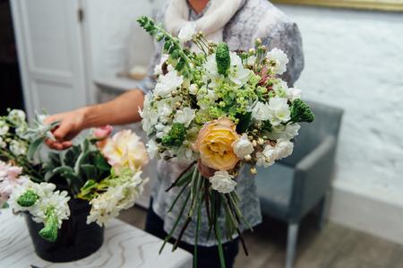 Florist finishing beautiful and rich spring flower arrangement Stock Photo