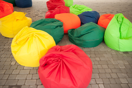 footstool: many colorful soft beanbag seats. under a canopy for relaxing Stock Photo