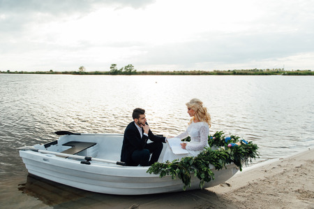portly: Happy young couple with a bouquet and a wreath hug sitting in a boat on the lake and sky background, lifestyle, love, relationships Stock Photo