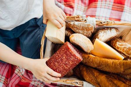 comiendo pan: small arms boy takes food out of the basket on a picnic in the garden. Sausage , bread, cheese