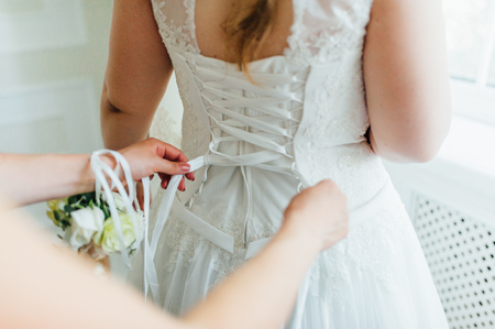 bridesmaids help to wear a wedding dress in the morning