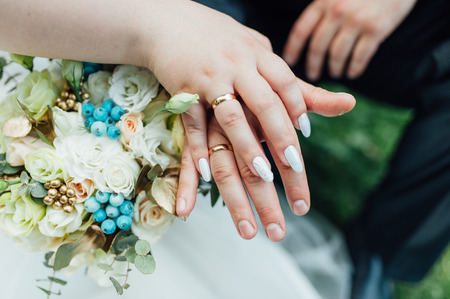 Hands and rings on wedding bouquet close up. Stock Photo