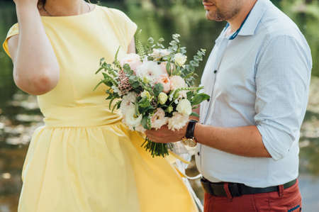 Beautiful wedding bouquet in hands of the groom. Stock Photo