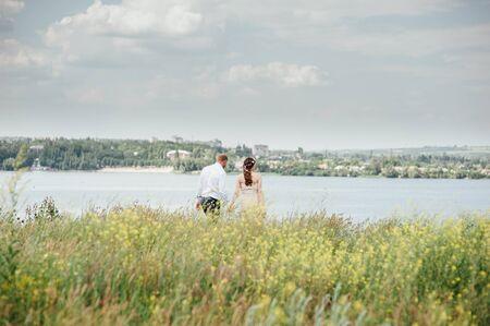 manos unidas: novia y el novio se está ejecutando con las manos juntas en un parque de la ciudad del sol por carretera Foto de archivo