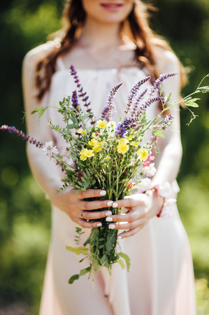 beautiful pregnant woman holding wildflowers at the park
