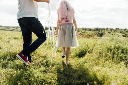 manos unidas: los amantes se est� ejecutando con las manos juntas en un sol de carretera del parque de la ciudad. pareja vestida con camisetas Rey y la Reina Foto de archivo