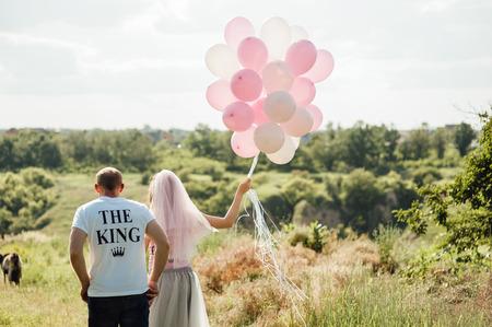 manos unidas: los amantes se está ejecutando con las manos juntas en un sol de carretera del parque de la ciudad. pareja vestida con camisetas Rey y la Reina Foto de archivo