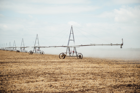 pivot: Mobile irrigation pivot watering on an empty field. Farmer watering the field after a successful harvest on a cloudy day