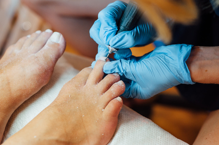 Master pedicure in steriele handschoenen vormen nagels en nagelriemen close-up. Hardware manicure. Concept lichaamsverzorging.