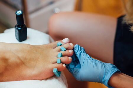 chiropodist: Master pedicure in sterile gloves shapes nails and cuticles closeup . Hardware manicure. Concept body care.