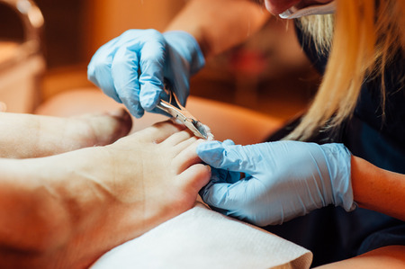 callus: Master pedicure in sterile gloves shapes nails and cuticles closeup . Hardware manicure. Concept body care.