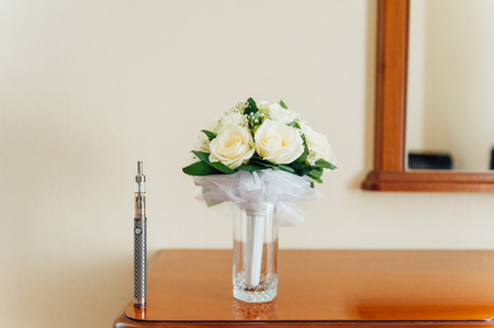 big electronic cigarettes near wedding bouquet on table