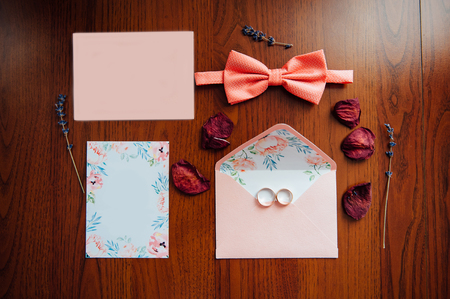 Blank greeting card with flower on rustic wood background for creative work design. With bow tie and rings