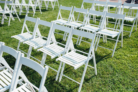 uniformity: Rows of white folding chairs on lawn before a wedding ceremony in summer