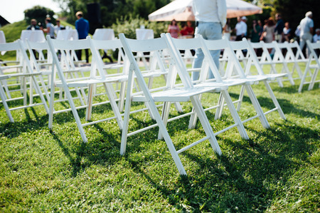 sameness: Rows of white folding chairs on lawn before a wedding ceremony in summer