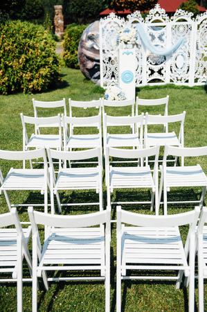 foresight: Rows of white folding chairs on lawn before a wedding ceremony in summer