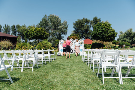 sameness: Rows of white folding chairs on lawn before a wedding ceremony in summer. Girl organizers suggest a final order before the guests arrive.