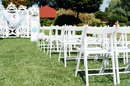 diagonals: Rows of white folding chairs on lawn before a wedding ceremony in summer