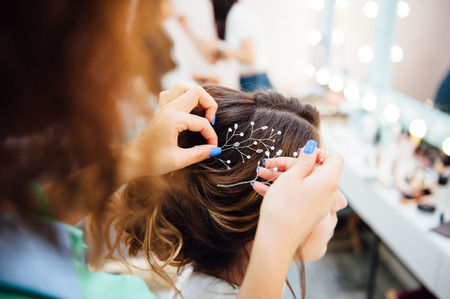 Hair stylist makes the bride a wedding hairstyle with fresh flowers Stock Photo
