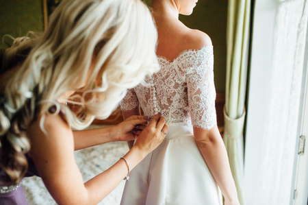 bridesmaids help to wear a wedding lace dress in the morning Standard-Bild