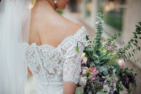 light hair: beautiful bouquet in hands of the bride is very stylish with light hair and lace dress Stock Photo