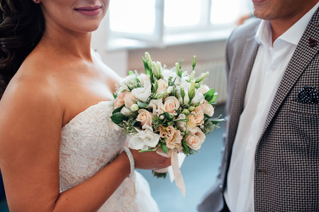 held: beautiful bouquet in hands of the bride is very stylish with light hair