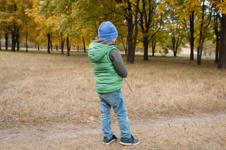 land scape: little boy in autumn land scape. man in a green jacket