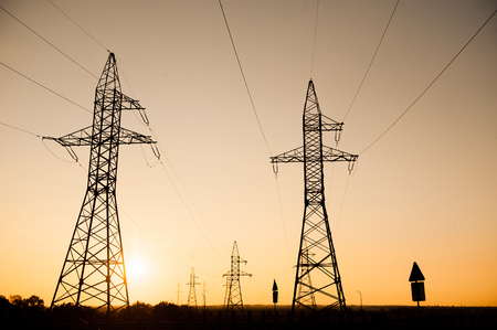 metal Bearing high voltage power line during sunset or sunrise.