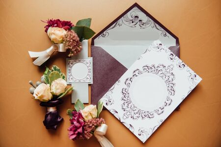stylish envelope with invitation cards with boutonniere groom and his friends