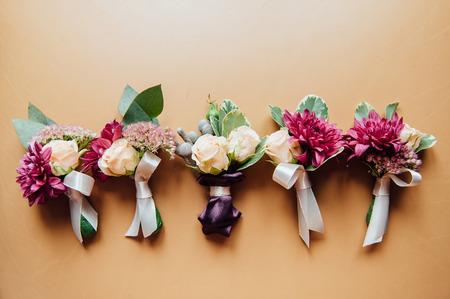 boutonniere: wedding boutonniere on a vintage wooden table. Stock Photo