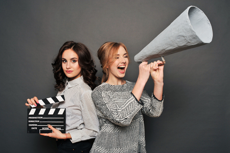 subordinated: two women inform about the beginning of shooting. With speakerphone and clapperboard. Stock Photo