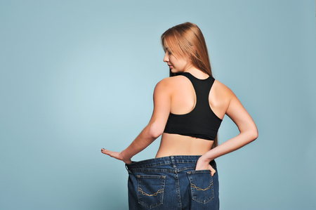 waistline: Women shows her weight loss. Isolated on blue background