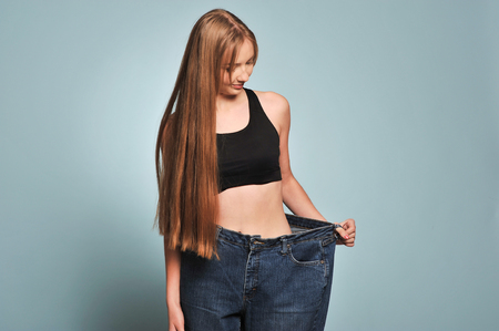 Women shows her weight loss. Isolated on blue background