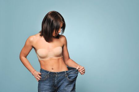 Fit young woman in loose jeans after losing weight isolated on blue background