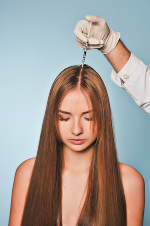 Handsome woman receives an injection in the head. The procedure makes male doctor in white gloves. The concept of mesotherapy. Thrust to strengthen the hair and their growth