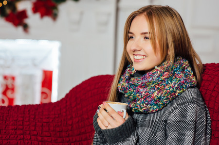 yule log: Beautiful girl is warming near fireplace while holding a cup of coffee in her hands