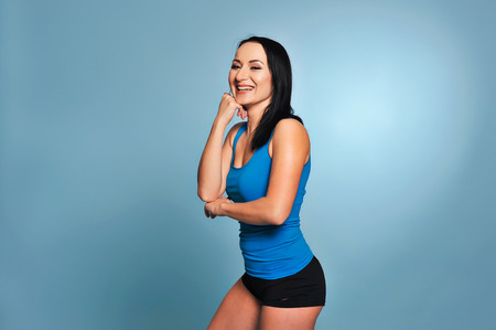 Pretty fit girl or fitness instructor posing and smiling isolated on blue background Stock Photo