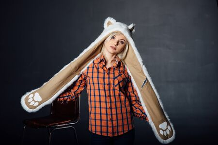 beautiful sexy girl wearing plaid shirt and white fur hat with funny ears. Close portrait on dark background Stock Photo