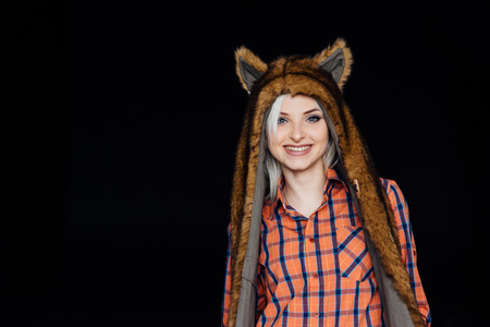 beautiful sexy girl wearing plaid shirt and brown fur hat with funny ears. Close portrait on dark background