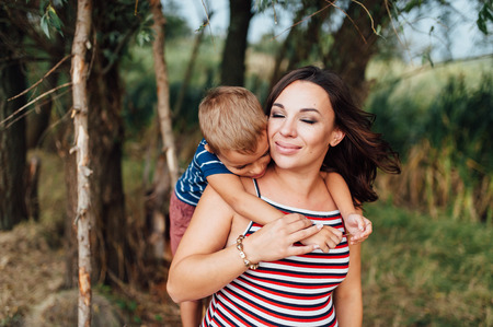 Pregnant woman in strip dress is hugging with her son. child sitting on the back of Mom