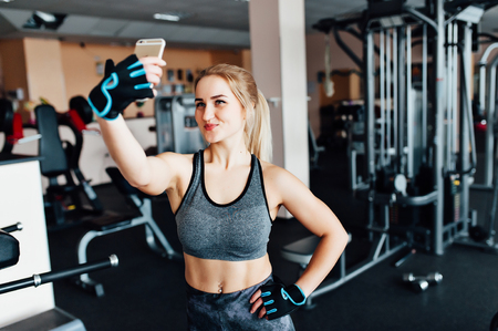 blondie: young beautiful sporty woman making selfie photo on smart phone in gym