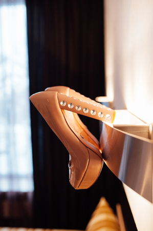 Beautiful bridal beige shoes hang on the wall lamp across from the window
