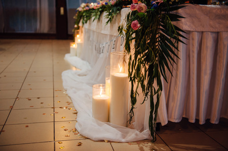 Wedding table for newlyweds or for any other event. Decorated with candles, flowers, ornaments and a white cloth