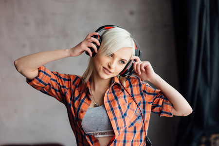 Happy blonde girl listening to the music at the window. girl dressed in an orange plaid shirt. woman holding hands headphones and smiling. Stock Photo
