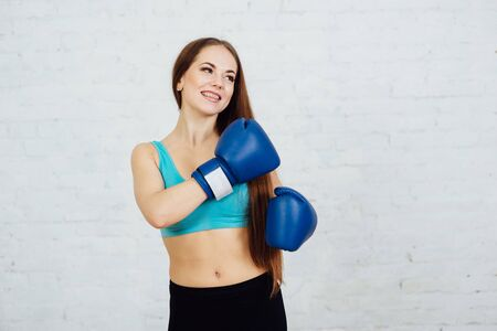 Beautiful boxer girl smiling with braces in blue gloves Stock Photo